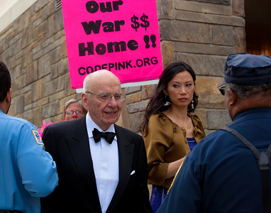 Media magnate Rupert Murdoch passes an anti-war protestor on the way to the National Correspondents Dinner