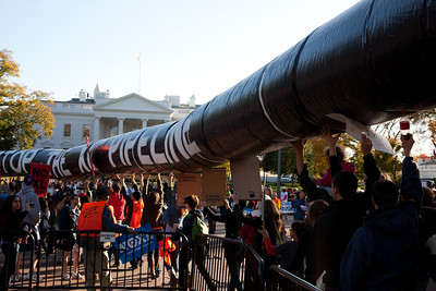 "Protestors march through Lafayette Park on the way to the White House in Washington DC carrying a long mock-up of a pipeline with the writing ""Stop the XL Pipeline"" on November 6, 2011."
