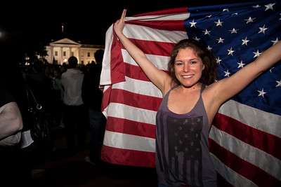 A jubilant Allyson Childress of Falls Church VA stands proudly behind the American Flag with the White House in the background. The announcement of the death of Osama Bin Laden sparked a spontaneous celebration at the north gate of the White House with chants of USA USA and the singing of the National Anthem. 1:20 AM on May 2, 2011 in Washington DC.