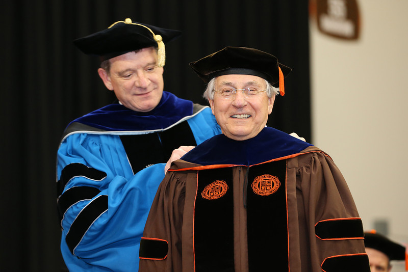Philanthropist Bob Sebo, right, of Salem, Ohio was surprised and thrilled to be recognized with an honorary doctorate, the highest honor bestowed by the University, during commencement exercises at Bowling Green State University on Friday,  May 3, 2013. Placing the robe on Dr. Sebo is BGSU Provost Rodney Rogers. (Marketing & Communications, BGSU)