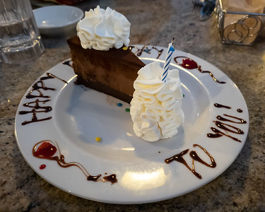 Of course I order a Godiva Chocolate Cheesecake.  Our waiter struggles to get the candle lit due to how windy it is...not that I was going to actually blow the candle out (since the pandemic pretty much killed that tradition).