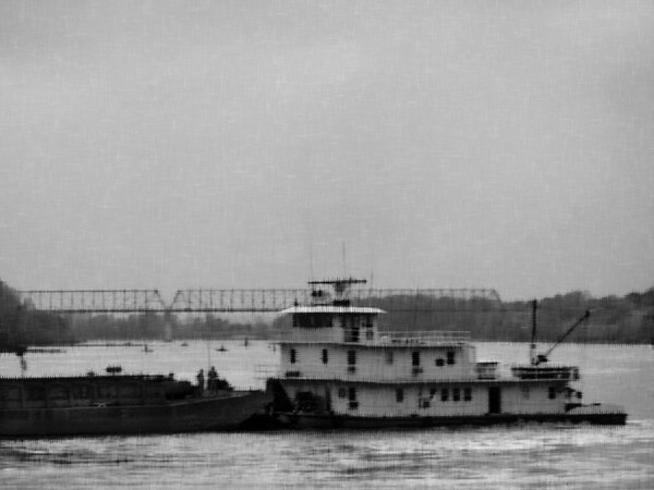 - MO ARK -<br /> This boat, the Mo Ark, is working the docks around Kansas City--<br /> shuttling barges where they are needed.<br /> This was shot on the Missouri river in November of 1970, just minutes before darkness fell.<br /> The original is a 35mm slide. The exposure on this shot wasn't very good <br /> since I was shooting into the western sky at sunset, trying to capture the color of the cloud cover.<br /> I still liked the subject matter and made this black and white and applied a watercolor paper filter.
