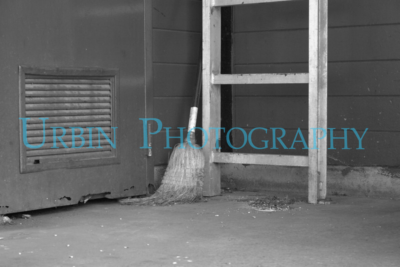 An abandoned broom at a shutdown restaurant.  Left in the corner when the last crew left. The spot where the building was is now a parking lot.