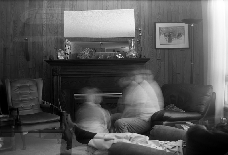 This photo was taken with a Kodak No. 2 Brownie model F (1929-1933). And as evident in the upper left corner, this was also a double exposure!<br /> <br /> The second exposure was a roughly 5 second exposure due to the low light levels in the room. The room was only lit by the big window on the right. John and Grandma are playing Snakes and Ladders. Papa Wilson is sleeping - I tried to frame the photo as to get all of Wilson in the shot but the ground glass of the view finder window coupled with the lower light made it difficult to see properly.<br /> <br /> Ilford Pan F+ developed in Kodak D76 1:1 for 10.5 mins @ 20C.