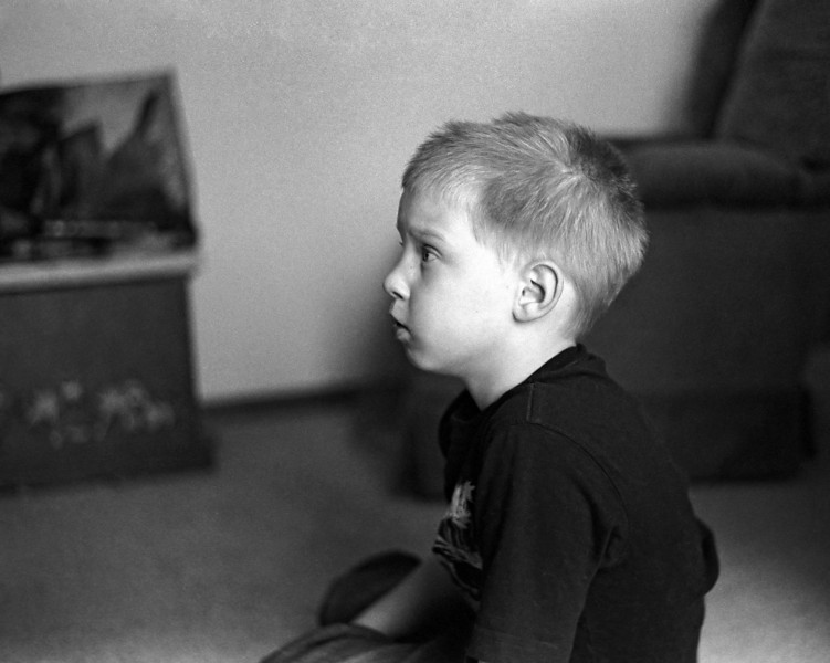 Photo of John in his toy room.<br /> <br /> Leica M5 with a Canon 50mm 1.8 lens, Kodak Tmax 400 developed using Kodak D76 for 8 minutes at 21C. This is from the very first strip that I developed myself.<br /> <br /> I finally got a true 'wet' darkroom set up in my basement. I choose this negative to make my first print. So this image was the first image I scanned from the first strip of b&w film that I developed myself - and the first to print in my darkroom.