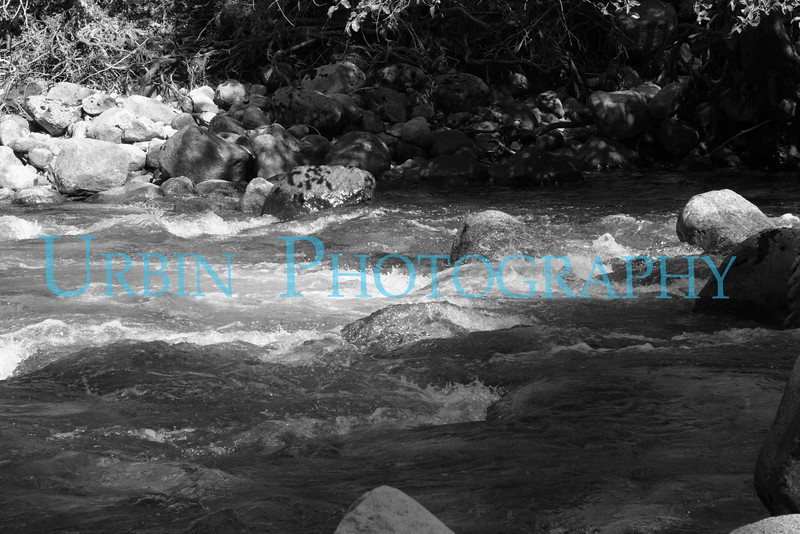 A black and white shot of the Merced River at Happy Isles.
