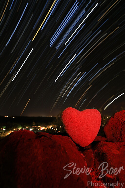Heart shaped rock with light painting and star trails