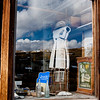 BE135.  Tailor shop with sky reflection in glass.