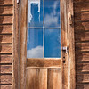 BE139.  Front door with remaining curtain, revealing sky reflection.