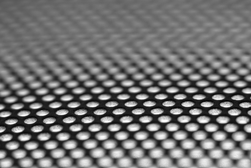 Macro shot of a 120mm computer fan grill sitting ona light table.