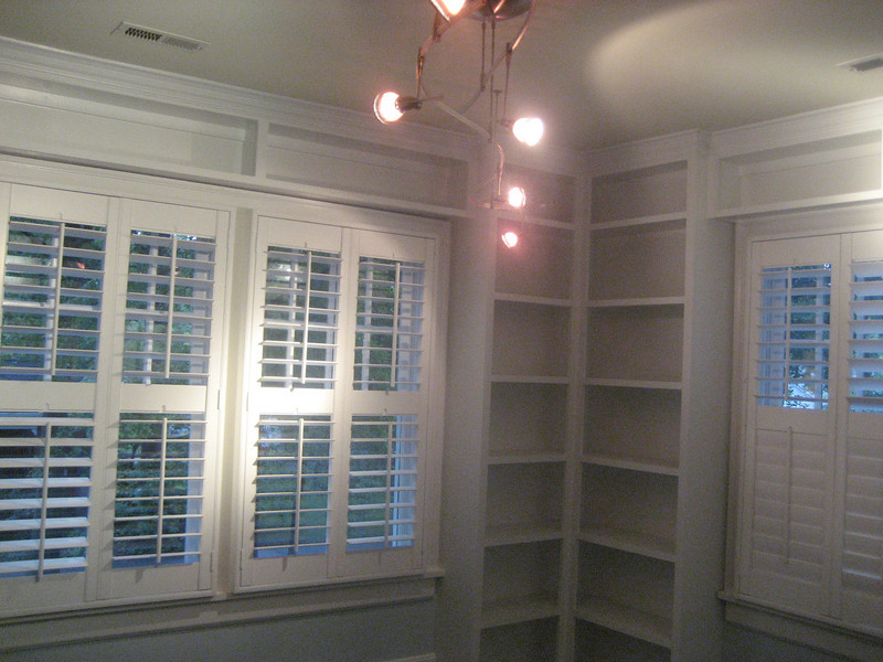 Childs bedroom corner bookshelves and collections displayed above windows