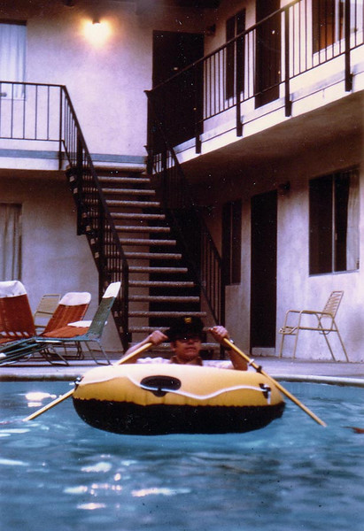 CAP'N DOUG<br /> Port Hueneme Apartments<br /> <br /> This is a shot of me in my 2-person inflatable raft in our apartment's pool in Port Hueneme, the first place my wife, Karen, and I lived in. It was a dumpy little place, but after she got a job at the local health clinic (she was an LVN), we were able to escape to nicer digs. I once rode my bicycle into this pool just to see what it was like. I learned you had to do a small wheelie just before entering, or else the bicycle stops and you don't, leaving a nice bruise on each leg from the handlebars. I never said I was a rocket scientist.