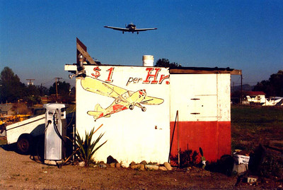 $1 PER  HOUR Here's something fun I ran across at Santa Paula Airport. Depending on how long that sign's been up there, it could've been true at one time. When I was taking flying lessons back in the late 60's and early 70's, I used to rent a Piper Cub for $3 per hour, so this is not such a stretch considering this shot was taken in 1973 and that looks like an Aeronca Champ painted there. (Actually, it looks like Don's.) It looks like it's been there a while, though. Boy, those were the days.
