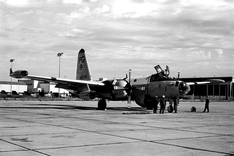 MY RIDE AWAITS<br /> Naval Air Station Dallas, Grand Prairie, Texas - 1974<br /> <br /> And here's my ticket home now, one of our SP2H Neptunes just waiting for the pilot to do some of that pilot stuff they always have to do. Those are parachute harnesses lying on the ground to the left of the guys standing by the nose, which we always wear when flying. (The actual parachutes are stowed on racks in the airplane, and we clip on if we need them.) A lineman stands at the ready with a fire extinguisher on the right. We always do that as a precaution when starting the engines.