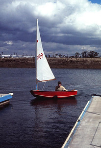 SABAT, AHOY! Anchorage Apartments, Oxnard  That's one of our neighbors, whose name I can't recall, sailing about in his Sabat sailboat. He actually let me take it out solo on this day, which proved to be a near-disaster. I did pretty well while in the lee of the apartment building, but when I moved into the gap between two of them, the wind completely flipped me over. Only by sheer instinct did I jump to the high side and get it righted again before it shipped too much water. How exciting!
