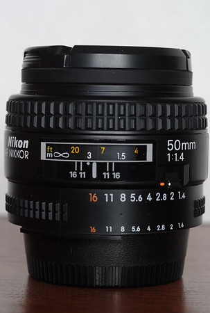 "This is the Nikkor 50 f/1.4 AF lens.  Back in the 50's and 60's, the better camera makers would bundle this kind of lens with their cameras as a ""kit"" lens (witness the Nikon F), before the advent of cheap consumer-grade zoom lenses.    There really isn't too much one can say about this focal length, except that you actually get the same field of view as a 75mm lens when it is used on Nikon ""DX"" format digital cameras such as the D40(x)/D50/D70/D80/D100/D200/D300/D2x.  A fixed focal length like this feels rather ""cramped"" to me when shooting indoors, so the real compelling reason to have any of the ""50's"" around is because of the speed, sharpness and relative lack of distortion.   Still, at 75mm, it approaches the portrait range, and I use it as a telephoto lens of sorts.  On 35mm, many photographers say that this lens represents the field of view of the eye, but others debate this point.  This lens performs quite well at its larger apertures from f/1.4 on upward.  With the 50 f/1.8,  the corners of images were quite soft from f/1.8 until f/2.8, where it gets quite close to this lens in sharpness.  It was best used stopped down to f/4 and beyond.  Still, there is a bit more vividness to the color rendition with this 50 f/1.4 optic, and the bokeh is more pleasant.  I was able to get this for quite a nice eBay price, and this is one of the better ""Made in Japan"" versions of the 50 f/1.4."