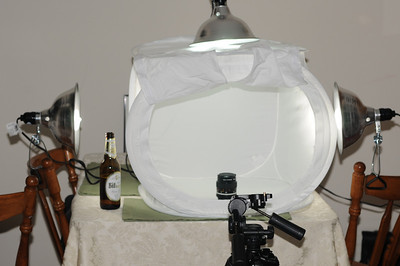 Moving up: my light tent and 3 clamp-on work lights with daylight compact-fluorescent light bulbs.  A nice cold beverage of choice can be a good influence in the creative process.