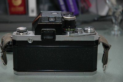 Rear view of Nikon F.  You can see the viewfinder (near center), film rewind crank (left), shutter speed selection (1/250 sec.), film advance lever, and shutter release.  The small button in the recess, left of the viewfinder, releases the viewfinder prism and also the focus screen inside.  The focus screen is of the split-image rangefinder type.