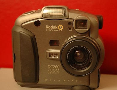 "My old workhorse, the Kodak DC 260, which I got back in December of 1998 (Merry Christmas to me!) for the princely sum of $1000 at CompUSA in Nashua, New Hampshire.  This was my very first experience with digital cameras, before they became the all the current rage.  At the time, this camera had one of the highest resolutions (1536x1024 when most offered only 640x480 VGA) and one of the first to offer USB support.  It is a fully automatic camera, thus it offers little control (no focus and no aperture control.) This camera is rather SLOW by today's standards.  Besides a 1-second shutter lag, it took as long as a Windows boot-up when first turned on.  Thus it was a bad camera for action shots at the airshow.  The initial set of rechargeable NiCad batteries weren't of very high capacity, as I found out whenever I would use the LCD viewer to see the results of my shots.  Digital cameras were not in the mainstream yet.  So all my relatives would crowd around the camera to look at all the pictures I took, marvelling at this new toy, then *POP*, the screen would shut off, the zoom would retract, and the battery would show empty, and I'd have to send everyone away...  A later set of NiMh batteries proved to be a fix to this problem.  There was the ability to control shutter speed and exposure value, and a scripting language allowed one to perform such functions as exposure bracket.  These programs were uploaded from the computer to the camera through the included software (or WinXP which can recognize this camera without additional software.)  There was no aperture control, and no real manual focus.  A Wide/Tele rocker switch and a built-in flash rounded out the feature set.  This was a consumer point-and-shoot camera all the way.  I still do use this camera once in a while, such as for taking pictures of my latest camera equipment.  The picture size comes out to a convenient ""web page""/eBay ad size, instead of downsizing the really high-rez pictures from my Nikon.   I really can't say that I ""did photography"" with this camera, rather that I merely ""took pictures.""  I have some pictures taken using this camera in a few of my galleries, namely the ""Maritime DC260 Edition"" and ""REALLY OLD Stuff"" galleries."