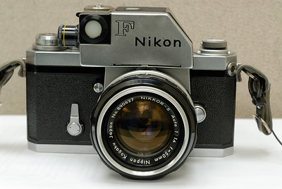 "Here is my Nikon Photomic F.  This is Nikon's entry into the professional 35mm film SLR camera market from 1959 to 1974.  My particular camera was manufactured in 1962, and I got it at a real bargain rate off of eBay.  The serial number of the body is 6478189, and an internet lookup of that number along with the fact that the body is topped by the Photomic viewfinder and meter indicates the year.  The camera is fully manual.  You choose aperture on the lens ring, and the shutter speed on the dial next to the shutter release and viewfinder.  The camera is fully modular, with interchangeable viewfinders, focus screens, and lenses of course.  What's more, it has mirror lockup (standard feature for professional cameras), and a mechanical self-timer.  All of the shutter settings work great, and this is built like a tank.  I'm sure it will be able to shoot for another 44 years.  From the looks of the pictures off the test roll, it's ready for many more great pictures.  The lens is the Nikkor 50mm f/1.4 by Nippon Kogaku (the old name for Nikon way back then.)  The word ""Auto"" on the lens ring refers to the fact that when the shutter is released, the aperture is automatically stopped down to the one chosen on the lens ring (This was considered an innovative and novel SLR technology back in 1959.)  Otherwise, these are manual focus lenses.  A fork-like attachment on the aperture ring couples with a pin in the Photomic viewfinder (under the ""Nikon"" logo) to mechanically transfer the aperture setting to the meter.  Unfortunately, the initial lens that came with the camera had fungus inside and oil on the aperture blades (yeck!) which made the action sticky.  Rather than try to get the lens serviced (lots of $$$ to disassemble, clean then reassemble the whole thing precisely) I simply chose to get another 50mm f/1.4 lens from eBay for $46...problems solved!  The other issue is that of the meter.  Back in 1962, when on-camera metering was being refined, many of the first meters required a mercury battery to provide 1.35 volts.  Mercury batteries also had a nearly constant voltage slope throughout battery life.  Unfortunately, mercury batteries are illegal in the US and many other countries.  A viable substitute is to use a 1.55v alkaline battery, however, the increased voltage throws off the metering, so either you need to get the meter recalibrated, or compensate with a different ISO setting. These days, I prefer to use a separate hand-held meter to figure out my exposure.  The alkaline batteries also degrade in voltage steeply near the end of battery life.  Zinc-air batteries (hearing aid) can provide the correct voltage, but once they're exposed to air, they only last a few months at most before they dry out and die.  Silver-oxide batteries require a fairly expensive adaptation process, but is regarded to be perhaps the most elegant solution.  Personally, I like to have a hand-held meter around.  Also, metering was not through-the-lens.  Incident metering is provided by a small screw-in translucent disc which is affixed to the meter ""eye"" next to the large ""F"" on the viewfinder.  I currently feel as though the Photomic viewfinder/meter is clunky (in both looks and usage), and would ditch it for the standard Nikon F meterless eye-level prism viewfinder if they weren't so expensive, since I use a Weston hand-held meter with this camera.  Several accessories accompanied this camera, including a threaded cable release, a tripod (old kind with screw-lock legs), a Nikon Yellow filter for B&W shooting, a Honeywell Tilt-a-Mite flash, and a Vivitar 85-205 f/3.8 zoom lens."