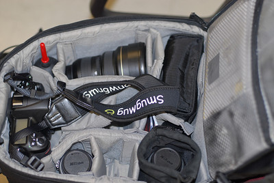 My current camera bag is a Lowepro Mini Trekker AW.  So what's in the bag?  Here it is...   Nikon D300 Camera with Nikkor 50mm f/1.4 lens. Spare area for Nikkor 50mm f/1.4. Nikkor 18-70 f/3.5-4.5 zoom lens. Nikkor 14-24mm f/2.8 Nikon SB-600 flash. Nikkor Micro 55mm f/2.8 Ai-S. Nikon PK-13 extension tube for Nikkor Micro 55mm. Manuals, batteries, memory cards, etc.