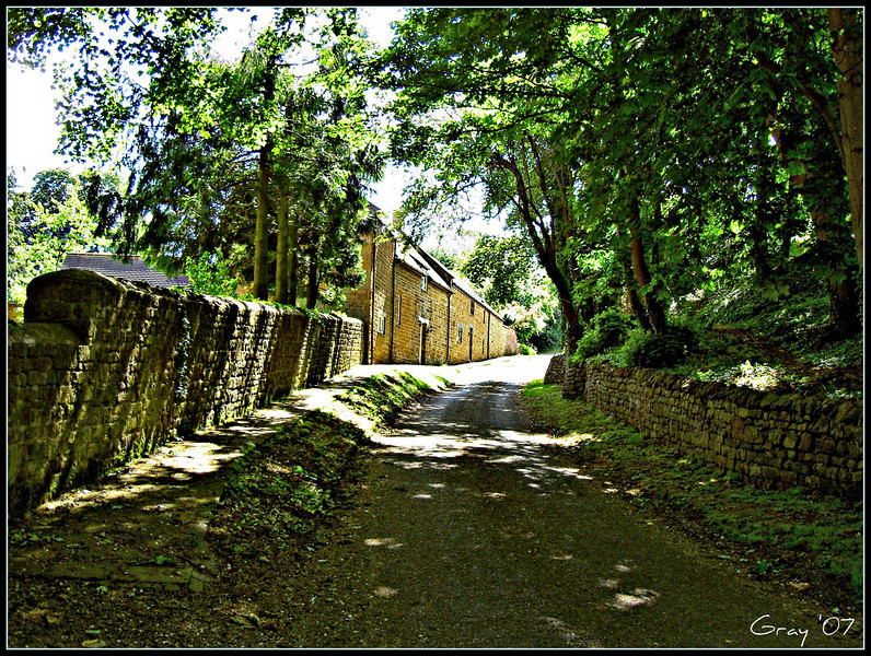 Sun-dappled Dark Lane; Wroxton, England <br /> Passing the Buttery; former stables for Wroxton Abbey, now used for classes and dining.