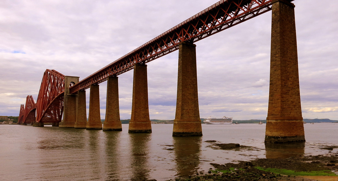 The Forth Bridge is a cantilever railway bridge over the Firth of Forth in the east of Scotland, to the east of the Forth Road Bridge, and 14 kilometres (9 mi) west of central Edinburgh. It was opened on 4 March 1890, and spans a total length of 2,528.7 metres (8,296 ft).