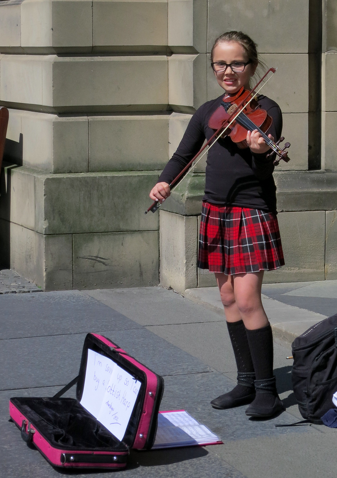 Young girl fiddling on the street to raise money for a school trip