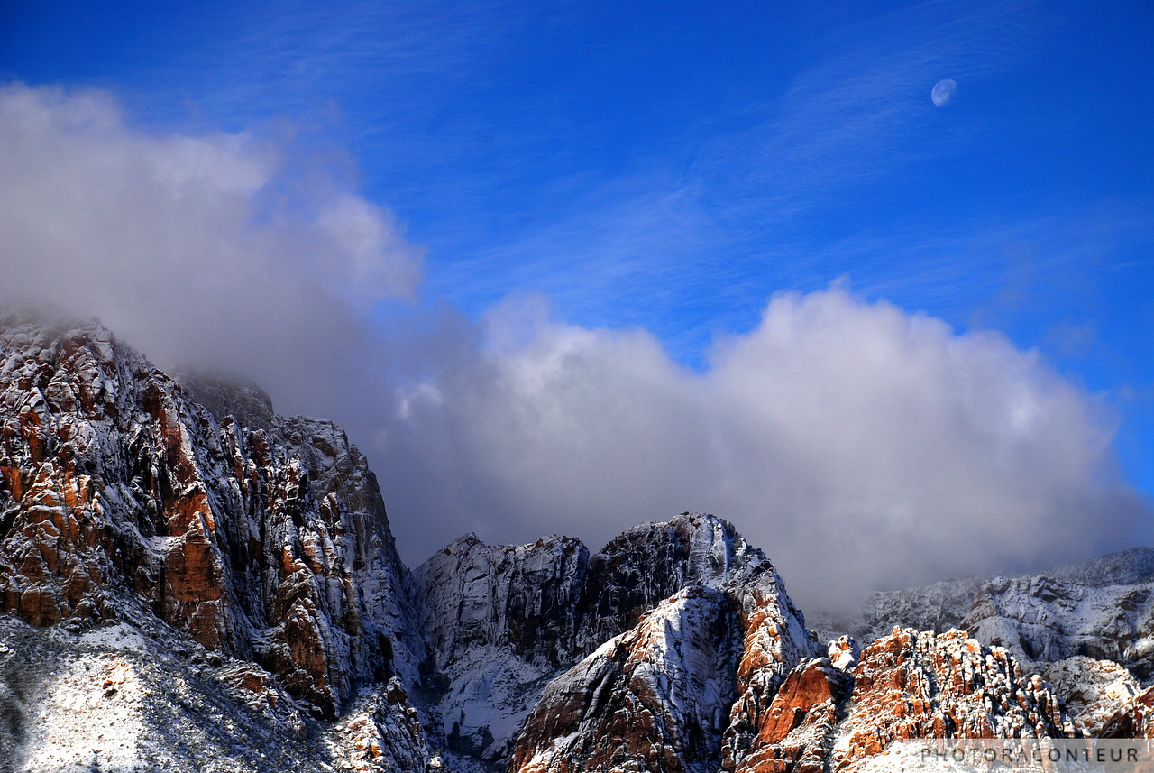 """Snow and Moon, Red Rock Canyon"" ~ On a rare snowy day in western Las Vegas, I headed to the nearby Red Rock National Conservation Area to take some photos of the snow-covered mountains and foothills.  I noticed where the path of the setting moon was heading, so I looked for a location and composition to capture the moon before it disappeared into the clouds that were rolling over the peaks.  The result is one of my personal favorite photos of Red Rock."