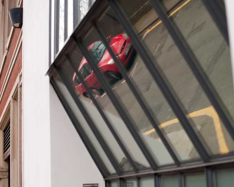 Red car reflected in angled window.