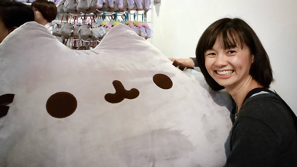 Valerie hugs the large Pusheen plush toy while waiting in line for the booth