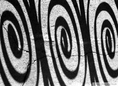 """Charleston Iron Swirls"" ~ Photo of swirls created by shadows of wrought iron on a historic building in historic Charleston, SC.  Note the cracks in the concrete surface of the porch."
