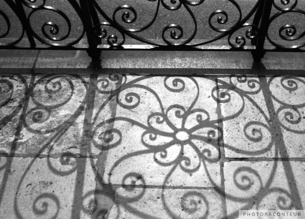 """Shadow Swirls at the Old Exchange"" ~ Historic downtown Charleston in South Carolina has one of the highest concentrations of  finely crafted iron fences and gates in the world.  Some of my favorite wrought ironwork in Charleston is the balusters and railing at the Old Exchange Building (c. 1771).  The location on East Bay Street at the end of the east-west corridor of Broad Street sets up this ironwork for some remarkable shadows such as these.  Cast against the texture of masonry flooring at the entrance to the Old Exchange, these shadows make for one of my personal favorite compositions featuring ironwork.  Also see ""Shadows & Stairs"" for another great composition of shadows and iron at the same building."