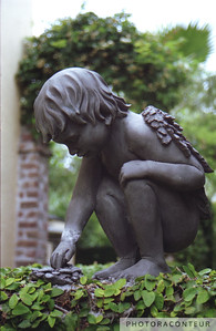 """Charleston Garden Angel"" ~ Carefully composed photo of small angel statue at the entrance of a hidden garden in historic Charleston, SC."