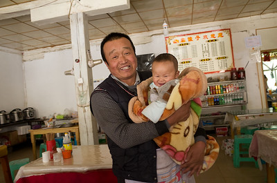 Restaurant proprietor from Jinan, Shandong Province, with grandson, Xianggelila Village