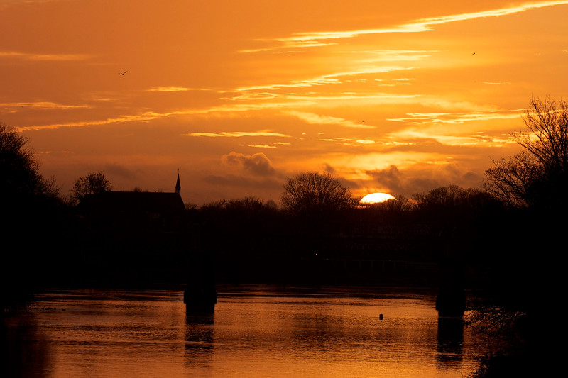Dawn over the Thames at Kew Railway Bridge and Strand-on-the-Green in Chiswick with St Paul's Church in the background.