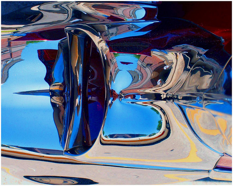 This is looking down on a 1957 Chevrolet tail light. The colors were provided by the clear blue sky, a pink brick building behind the car, the car's rich red paint, light tan/grey pavement, and yellow stripes on the parking lot. No touch ups were done.