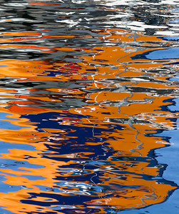 A tall orange and blue smokestack with a red logo on it produced this reflection. Ketchikan.