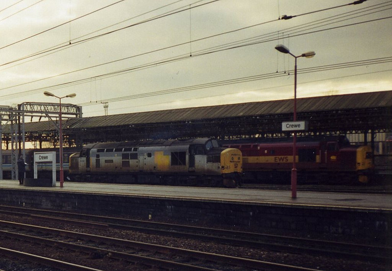 37261 light engine at Crewe as 37401 passes behind with a First North Western service for Holyhead. December 1998.
