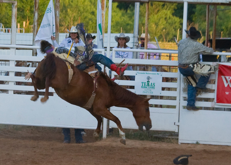 This guy should win a medal. Notice, all four feet of this bronc are off the ground.  In the next few shots, this guy is able to hang on!