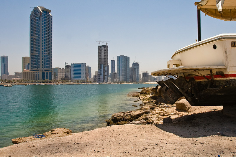Townscape featuring a power boat alongside Sharjah Creek