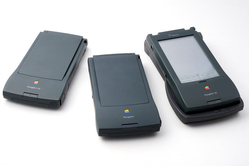 Three Apple Newtons. Left to right: a MessagePad 120 (French localization, 1994), a MessagePad 110 (US Localization, 1994) and a MessagePad 120 (US Localization, 1996) with its charging station.