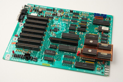 Apple ][ pictures. A late Apple //e motherboard. This one has been hacked: a switch can toggle between the use of the original Apple ROMs and a modified version of the ROMs.