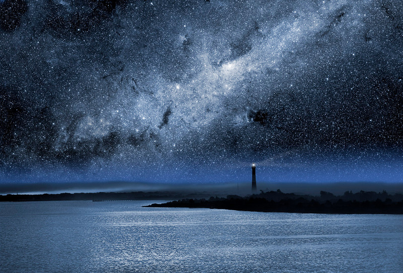 The Fire Island Light house near the western end of Fire Island at night with a bright Milky Way overhead.