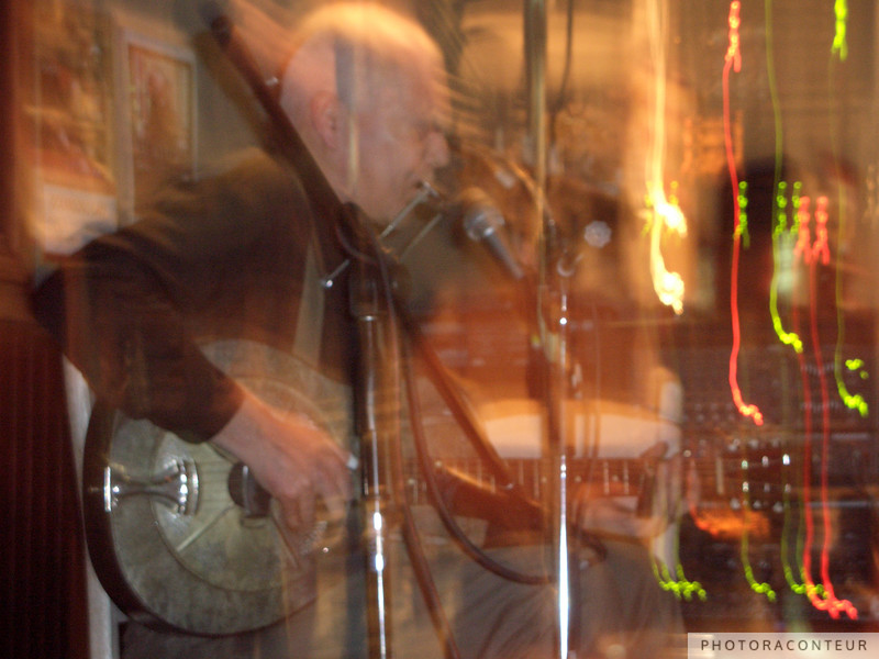 """""""Blues Man"""" ~ Abstract photo depicting the energy of Michael Pickett playing the harmonica and National resophonic guitar in Charleston, SC.  (Photo by Benjamin Padgett)"""