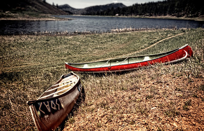 At the end of a long, dry summer canoes lie on the crisp grass at Lake Simpatico in Forest Lakes, Colorado.