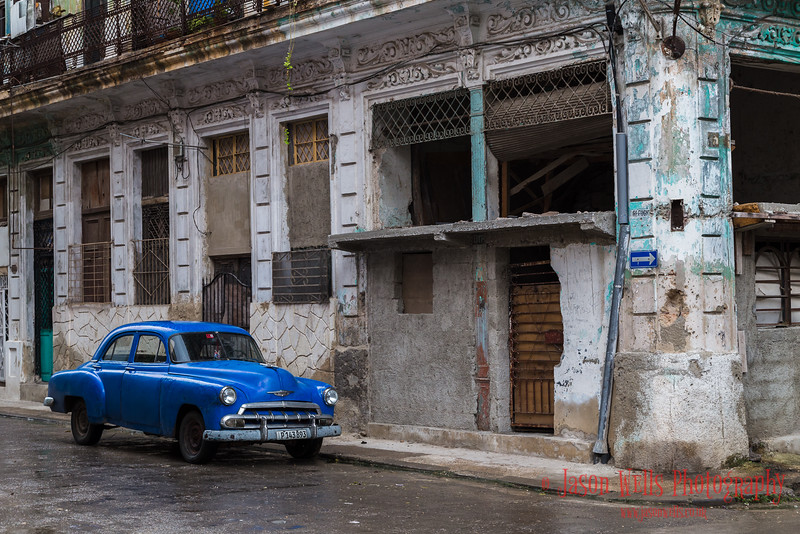 Old timer parked by a dilapidated building