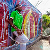 Youth leans on artwork painted by Laventille residents