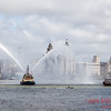 Tug spraying water in front of the Three Graces.