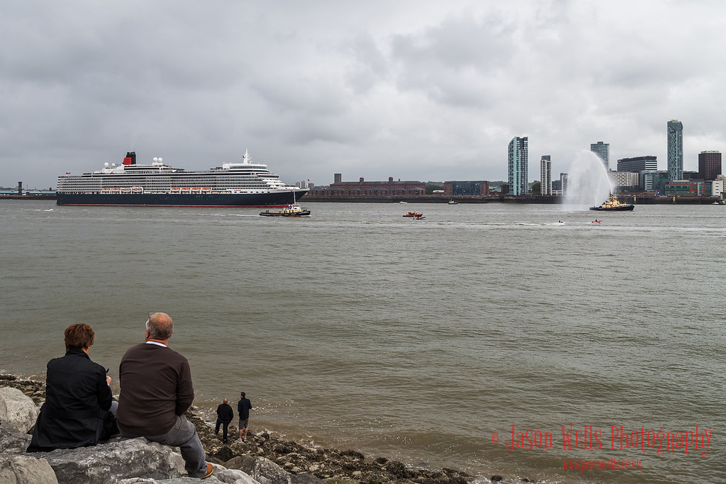 Queen Mary Two leads the procession down the River Mersey.